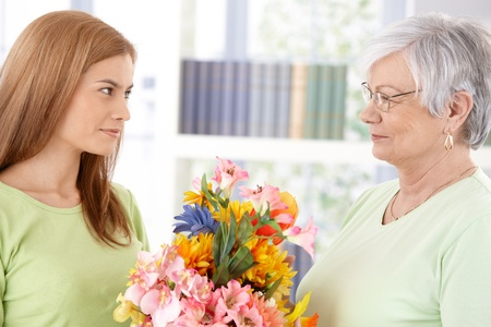 Attractive young woman greeting her mother at mothers day, giving flowers. photo
