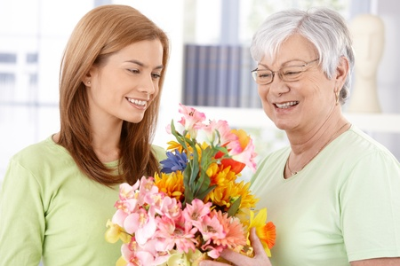 Elderly mother getting flowers from young daughter at mother's day, both smiling. Stock Photo - 9209313