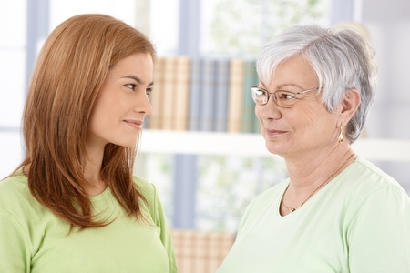 Senior mother and attractive daughter smiling at each other affectionately. photo