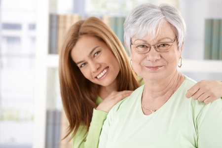 happily: Portrait of elderly mother and daughter smiling happily. Stock Photo