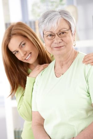 madre e hija: Madre Senior y atractiva hija joven sonriente felizmente, mirando a la c�mara.