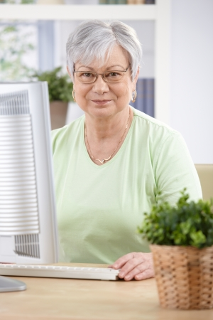 Portrait of elderly woman sitting at desk, having computer, smiling. photo