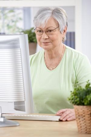 senior ordinateur: Femme Senior assis au comptoir, naviguer sur internet � la maison.