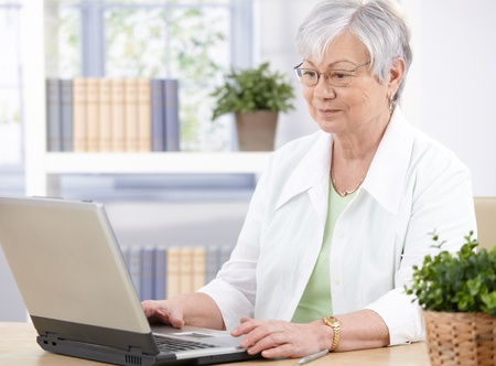 Old lady sitting at desk at home, using laptop. photo