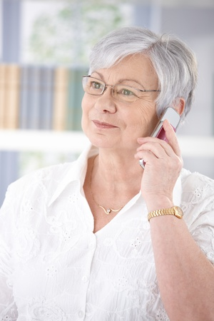 Old lady talking on mobile phone, smiling. photo