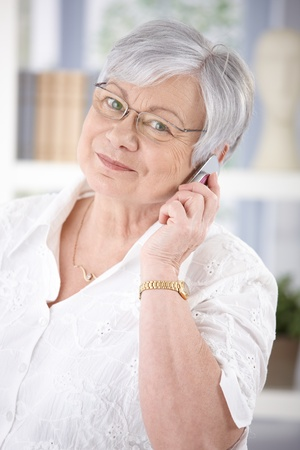 old phone: Cheerful senior woman talking on mobile, smiling, looking at camera.