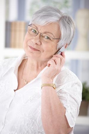 Cheerful senior woman talking on mobile, smiling, looking at camera. photo