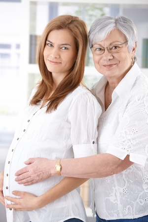 Attractive pregnant woman and senior mother hugging, smiling. photo