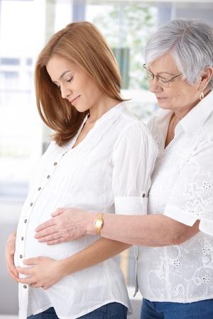 ambos: Madre Senior abarca embarazadas hija, ambos sonriendo.