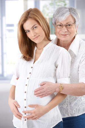 Senior woman hugging her expectant daughter, both smiling happily, looking at camera. photo