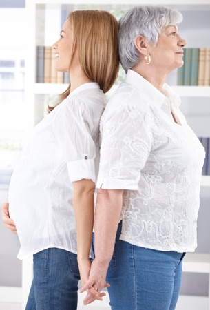 Pregnant woman and senior mother standing back-to-back, holding hands, smiling. photo