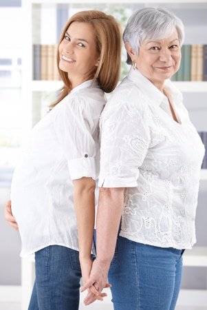 Senior mother and pregnant daughter smiling happily at camera, standing back-to-back. Stock Photo - 9209150