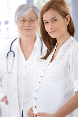 Portrait of young attractive pregnant mother and doctor, smiling. photo