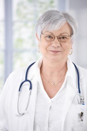 kindly: Portrait of kindly smiling senior doctor standing at hospital corridor.