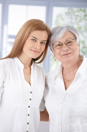 two generation family: Portrait of senior mother and attractive adult daughter, hugging each other, smiling. Stock Photo