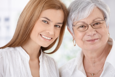 mature old generation: Closeup portrait of young attractive woman and senior mother, both smiling, looking at camera. Stock Photo