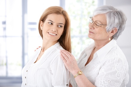 Senior mother and adult daughter smiling happily. photo