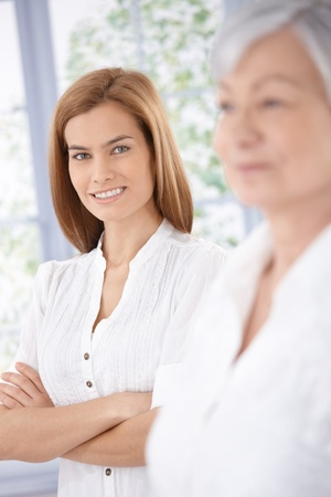 Portrait of attractive young woman smiling happily, senior mother standing at background. photo