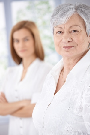 Portrait of elderly woman smiling, young woman standing at background. Stock Photo - 9208697