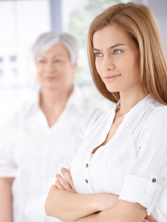 Attractive young woman standing arms crossed, senior woman standing at background. photo