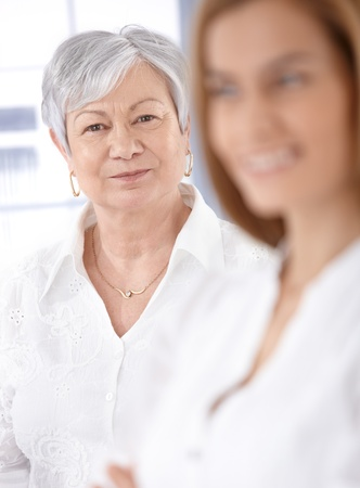 Portrait of smiling mature lady, young woman standing at background. photo