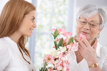 mature old generation: Pretty woman greeting her mother at mothers day, giving flowers, both smiling. Stock Photo