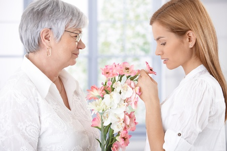 Senior mother holding bouquet in hand, adult daughter smelling flower. photo