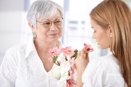 Mature mother and young daughter smelling flowers, smiling. photo