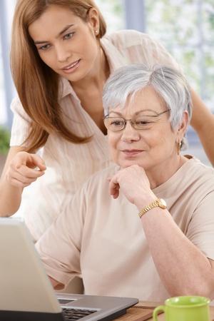 senior ordinateur: M�re Senior naviguer sur internet, jeune fille aider. Banque d'images