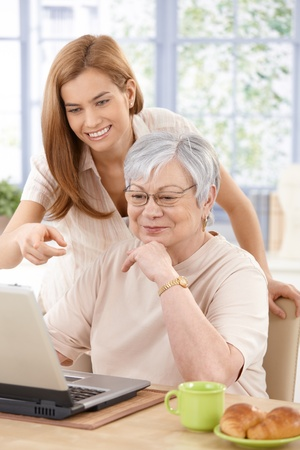 Mother and adult daughter using laptop, having fun, smiling. Stock Photo - 9209141