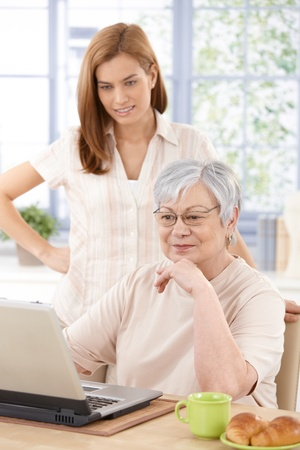 Grandmother and granddaughter browsing internet at home. photo