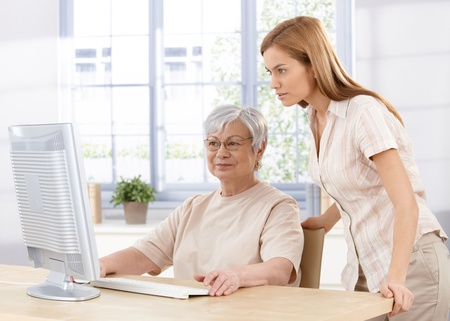 Senior mother and young daughter using computer at home, looking at screen. Stock Photo - 9208693