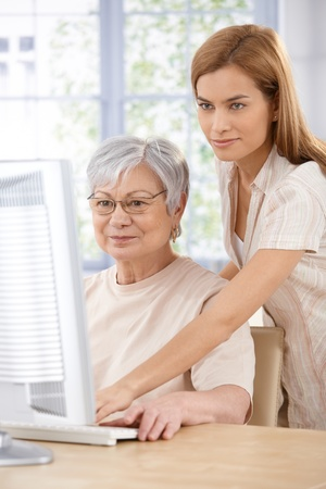 helping people: Mother and adult daughter browsing internet at home on computer. Stock Photo