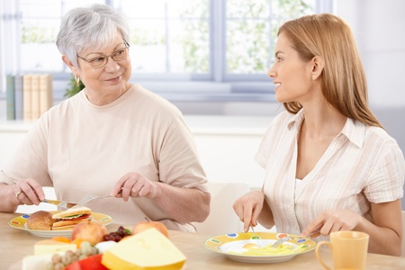 having lunch: Young woman having lunch with her mother, talking, smiling. Stock Photo