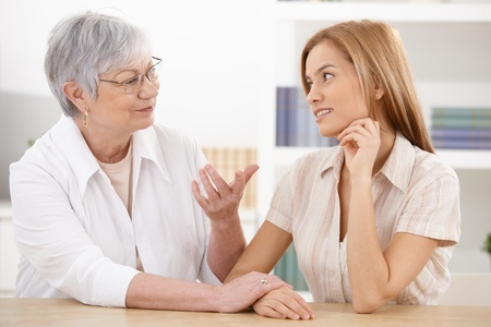 Young woman visiting grandmother at home, chatting, smiling. photo
