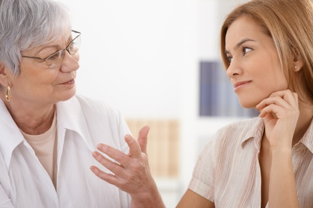 at each other: Senior mother and attractive daughter looking at each other with affection, talking, smiling. Stock Photo