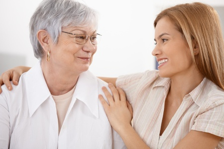 at each other: Attractive young woman hugging senior mother, smiling affectionately.