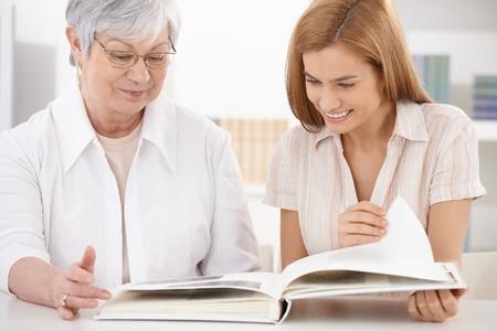 Senior mother and attractive daughter looking at photo album, having fun, smiling. photo