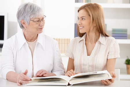 Young woman and grandmother looking at photo album at home, having fun, smiling at each other. Stock Photo - 9209115