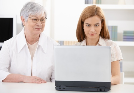 Beautiful young woman and senior mother browsing internet on laptop, smiling. Stock Photo - 9208639