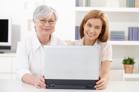 Mature woman and young attractive daughter using laptop at home, smiling happily. photo