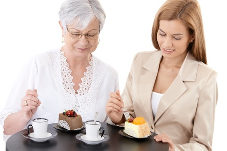 Senior mother and young attractive daughter eating cake, drinking coffee at coffee shop, smiling. photo