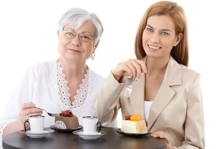 Grandmother and granddaughter sitting at table at coffee shop, eating cake, drinking coffee, smiling. photo
