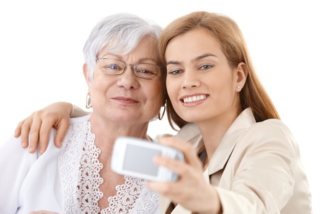 Senior mother and attractive daughter hugging each other, taking photo of themselves by digital camera, smiling happily. Stock Photo - 9208609