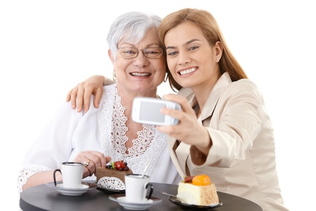 happily: Senior mother and young daughter sitting at coffee table, photographing themselves by digital camera, smiling happily.