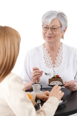Senior woman sitting at coffee table, eating a piece of cake, smiling at young daughter sitting opposite. photo