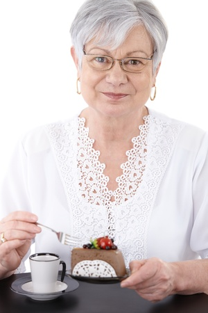 1 person only: Portrait of senior woman eating chocolate mousse cake, smiling at camera. Stock Photo