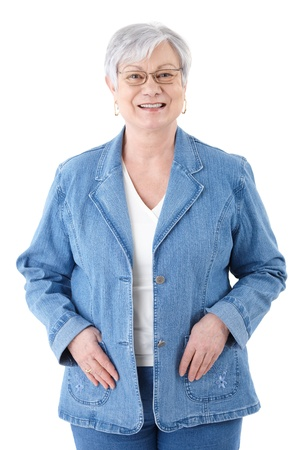boomers: Happy senior woman standing over white background, wearing denim jacket, smiling.