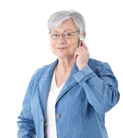 only one senior: Elderly lady standing over white background, talking on mobile phone, smiling.