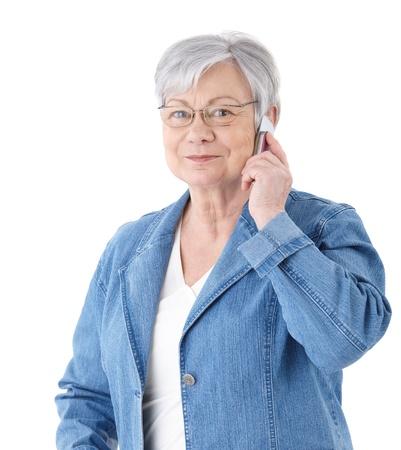 actief luisteren: Oudere dame permanent over witte achtergrond, praten over mobiele telefoon, glimlachend.